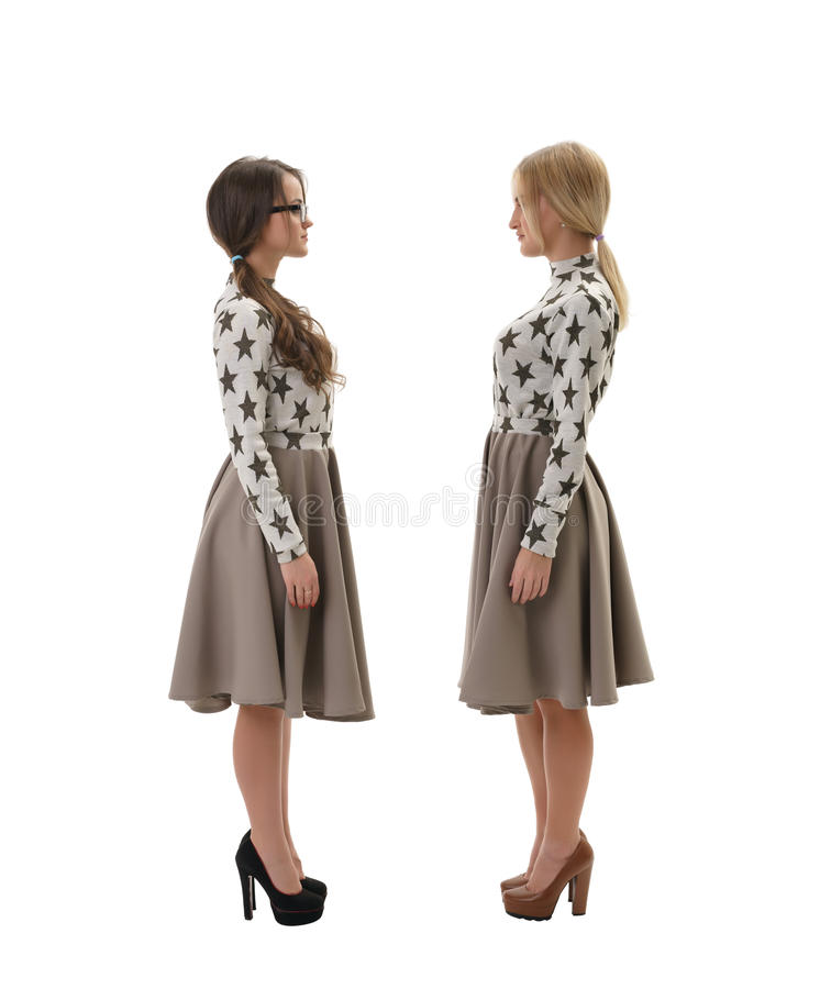 Deux femmes portant les mêmes vêtements d'isolement sur le blanc photos stock