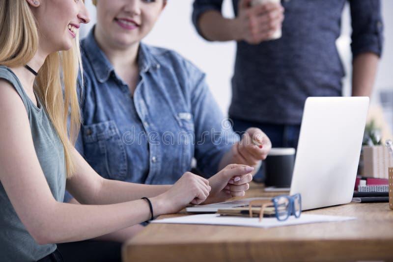 Deux femmes s'asseyant avec l'ordinateur portable image libre de droits