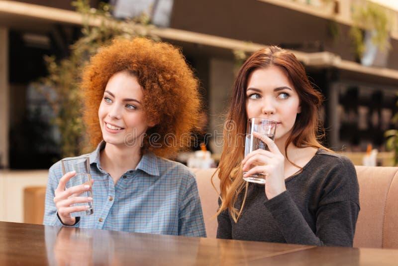Deux femmes s'asseyant en café et eau potable  photos stock
