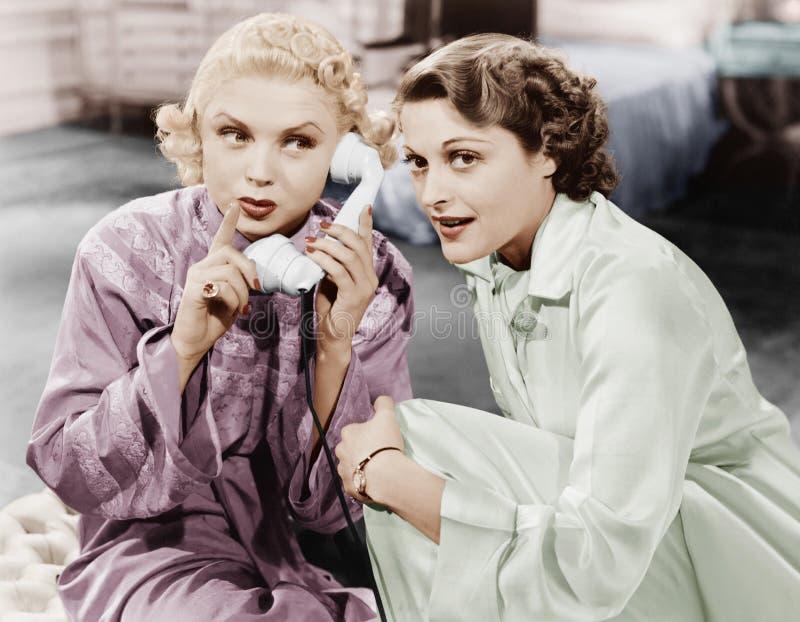 Deux femmes s'asseyant ensemble et écoutant sur le récepteur téléphonique (toutes les personnes représentées ne sont plus long au image libre de droits