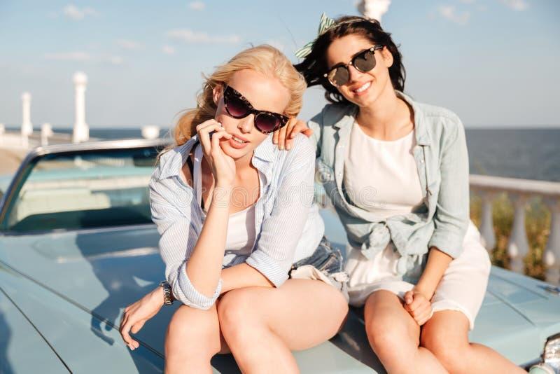 Deux femmes s'asseyant sur le capot de voiture ensemble image libre de droits
