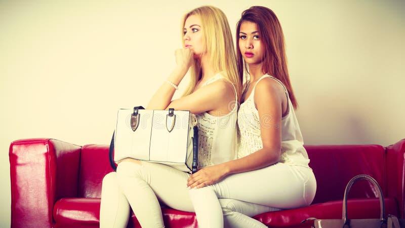 Deux femmes s'asseyant sur le sofa présentant le sac image libre de droits