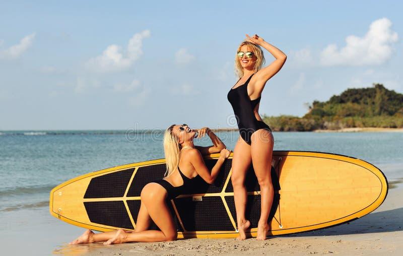 Deux femmes sexy posant près d'une planche de surf sur la mer photographie stock