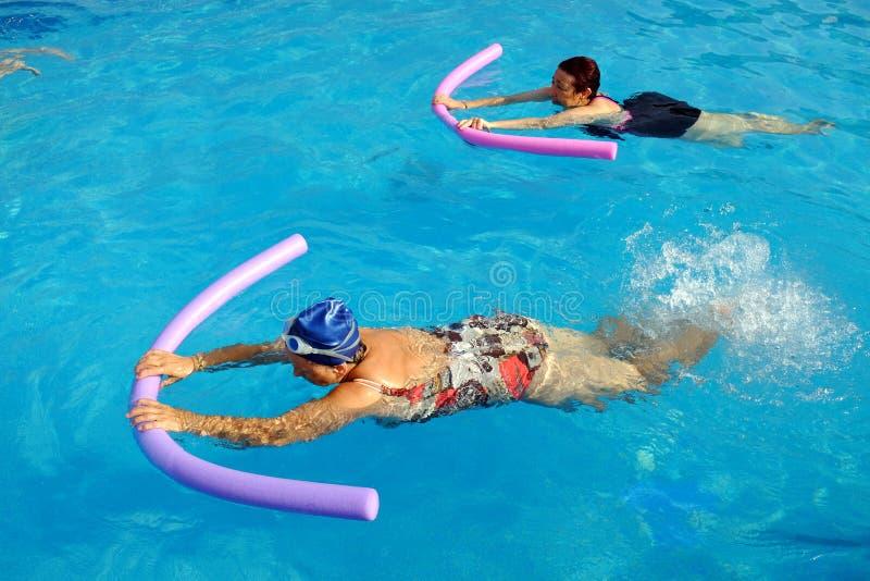 Deux femmes supérieures faisant l'exercice de natation dans la piscine image stock