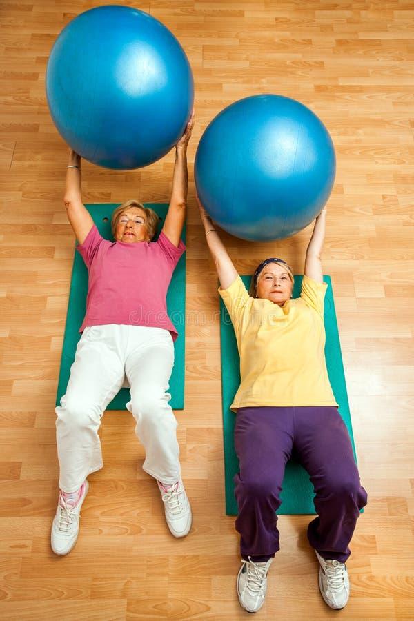 Deux femmes supérieures faisant la boule de gymnase s'exerce sur le plancher images stock