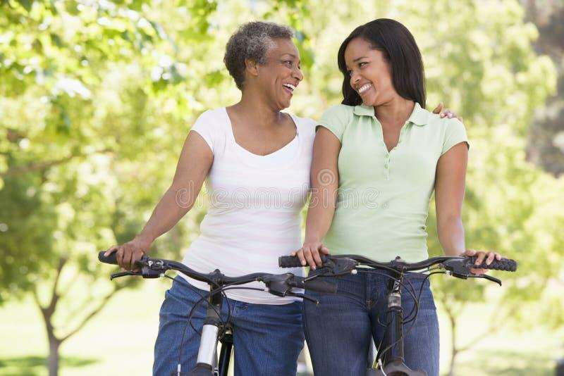 Deux femmes sur des vélos souriant à l'extérieur image stock