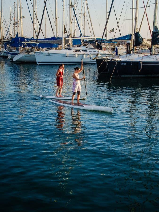 Deux femmes surfant sur des petites gorgées dans le port de Tel Aviv devant les bateaux et les yachts hébergés images libres de droits
