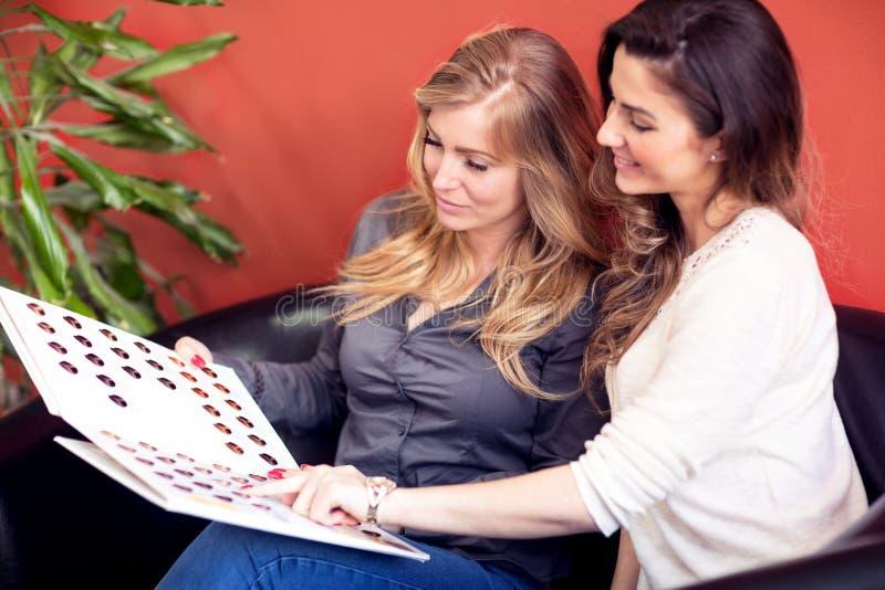 Deux femmes visitent le salon de beauté de cheveux pour faire nouveau dénommer image libre de droits