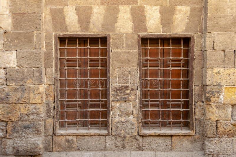 Deux fenêtres en bois adjacentes avec la grille de fer au-dessus du mur de briques en pierre décoré, le Caire médiéval, Egypte photographie stock libre de droits