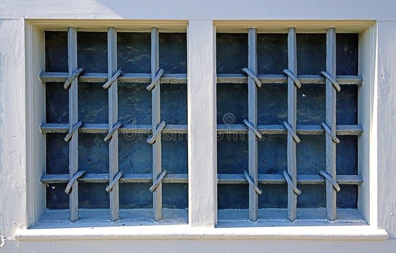 Deux fenêtres fermées par des grilles de fer travaillé image libre de droits