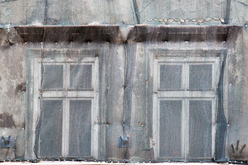 Deux fenêtres sur la façade de la vieille maison ont fermé la maille pour le repai photos stock