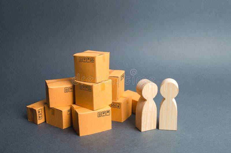 Deux figures humaines se tiennent près d'une pile des boîtes de craton l'acheteur et le vendeur, le fabricant et le détaillant di images stock