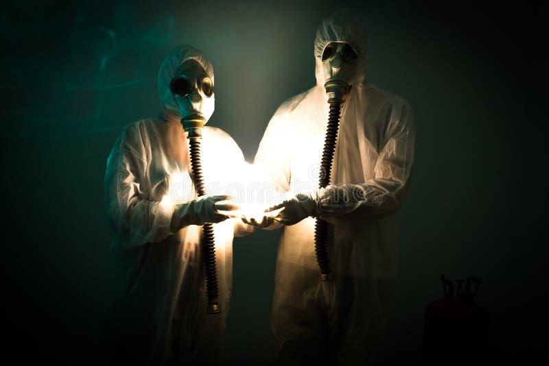 Deux figures portant des costumes de biohazard tiennent une lumière étrange photographie stock libre de droits
