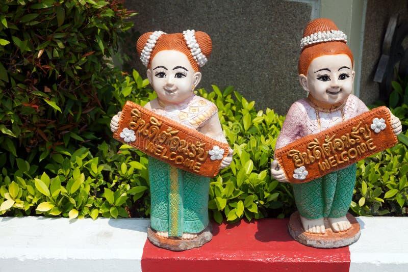 Deux figurines en céramique de filles thaïlandaises jugeant le connexion bienvenu anglais et thaïlandais images stock
