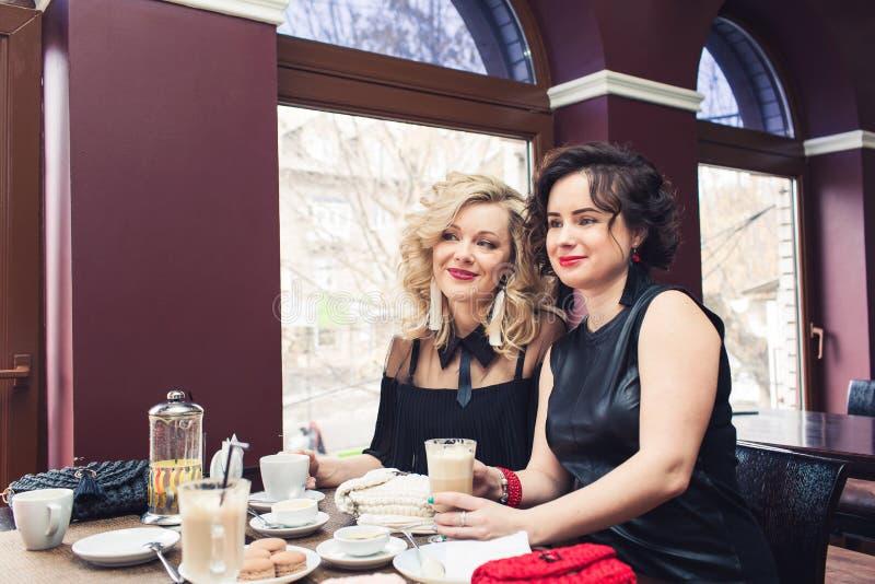 Deux filles élégantes s'asseyent à la table en café et boivent des boissons photographie stock libre de droits