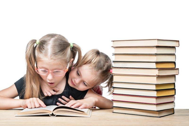 Deux filles étudiant le livre de surprise images stock
