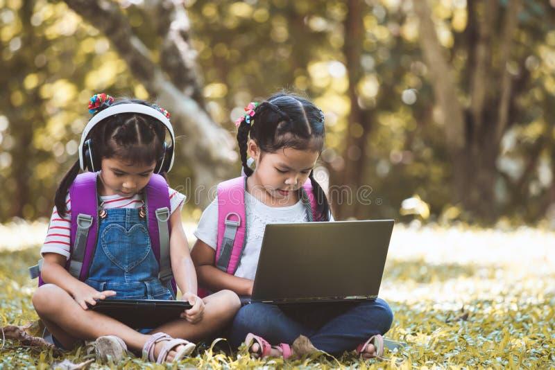 Deux filles asiatiques mignonnes d'enfant à l'aide du comprimé et de l'ordinateur portable dans le parc image stock