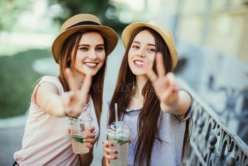 Deux filles attirantes joyeuses prenant un selfie tout en marchant le todether avec des cocktails sur la rue et montrant le geste photo libre de droits