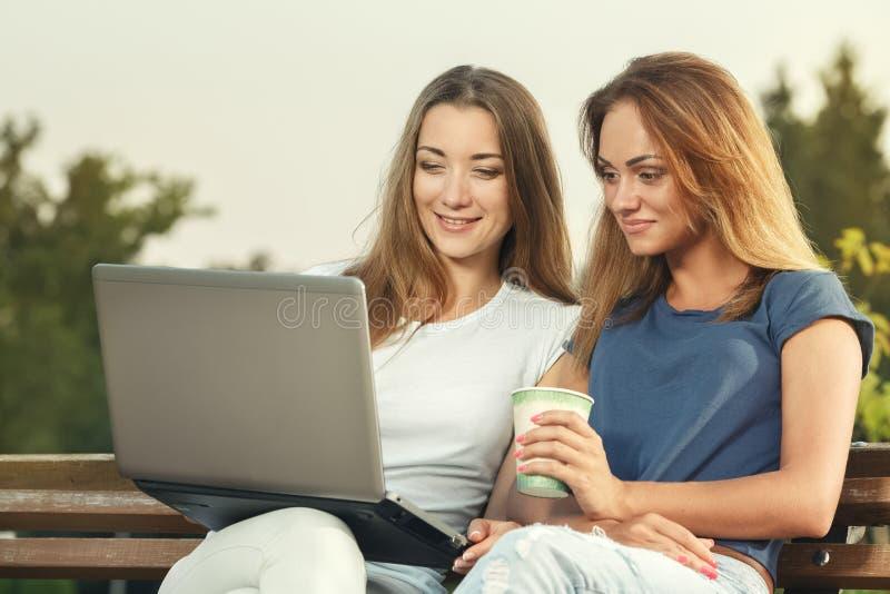 Deux filles attirantes s'asseyant sur le banc en parc photo libre de droits