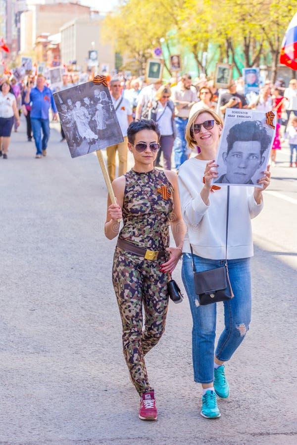 """Deux filles avec des portraits de leurs ancêtres dans l'action """"régiment immortel """" photo libre de droits"""