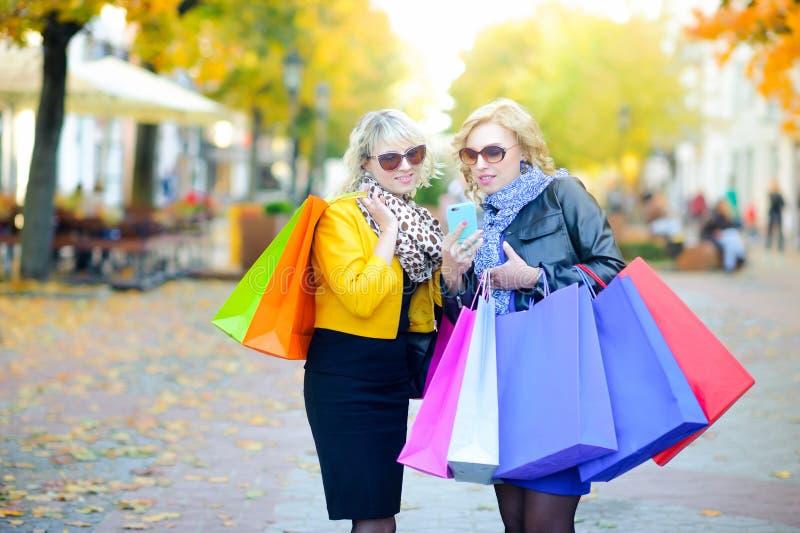 Deux filles avec des sacs à provisions font un ordre par le téléphone, faisant des emplettes en ligne photographie stock
