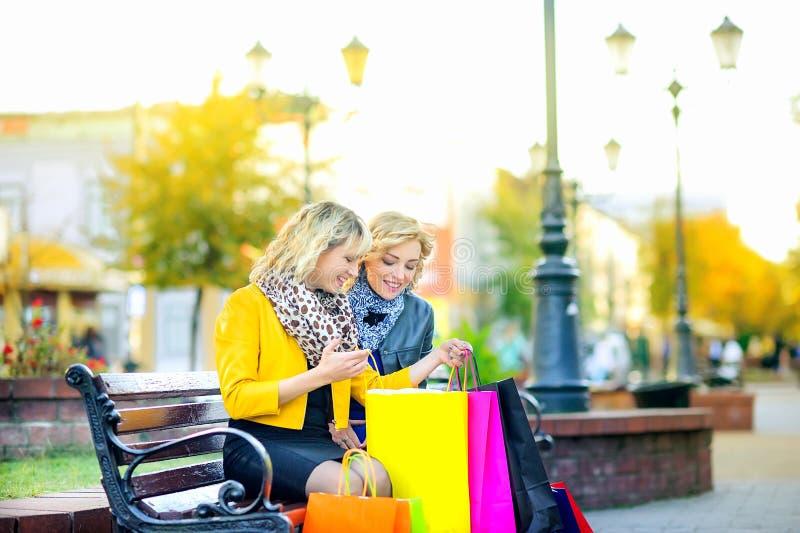 Deux filles avec des sacs à provisions s'asseyent sur un banc et considèrent des achats photographie stock libre de droits