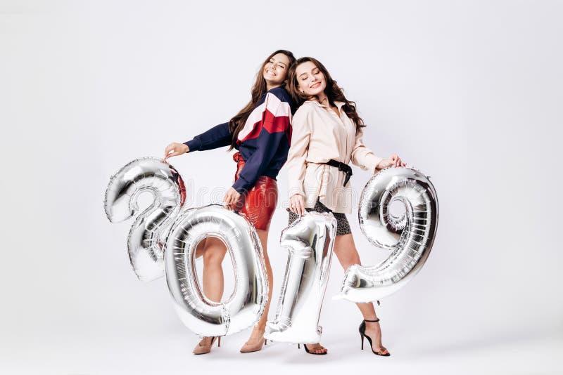 Deux filles avec du charme habillées dans les vêtements intelligents élégants tiennent des ballons sous forme de numéros 2019 sur photographie stock