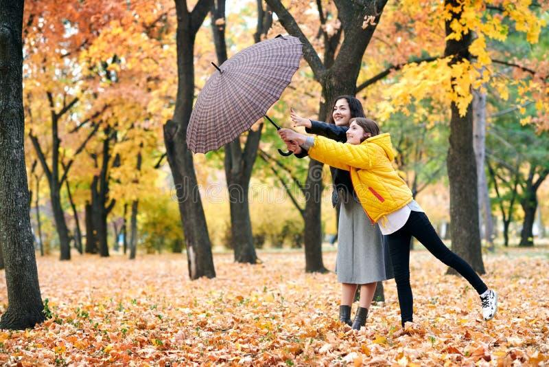 Deux filles avec le parapluie posant en parc d'automne Feuilles et arbres jaunes lumineux Ils imitent le vent photographie stock