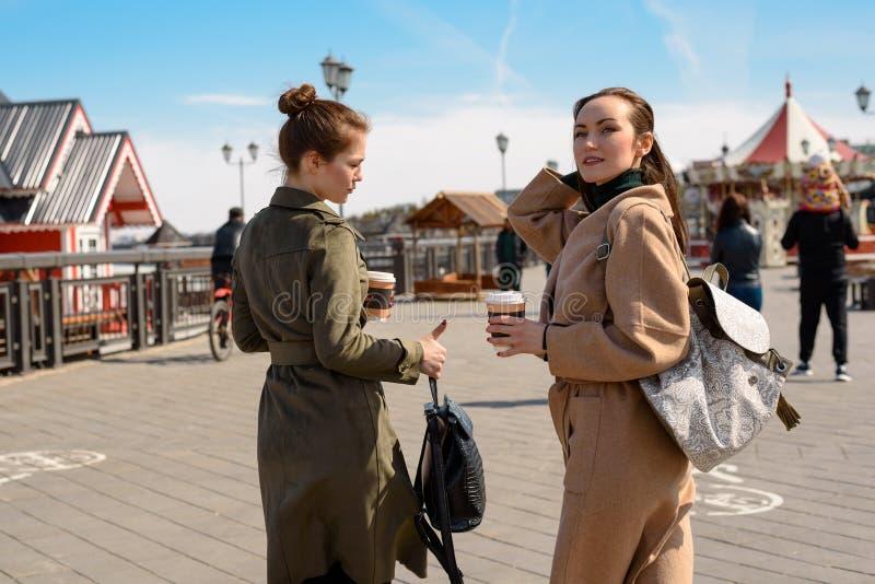 Deux filles avec les manteaux et les sacs à dos élégants marchent en parc avec des tours, vue arrière image stock