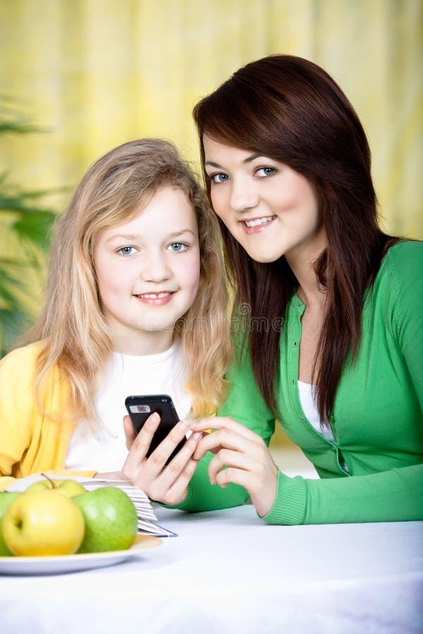 Deux filles avec un portable image stock