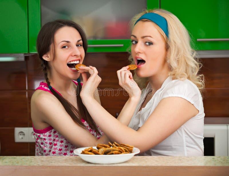 Deux filles ayant l'amusement avec des biscuits dans la cuisine image libre de droits