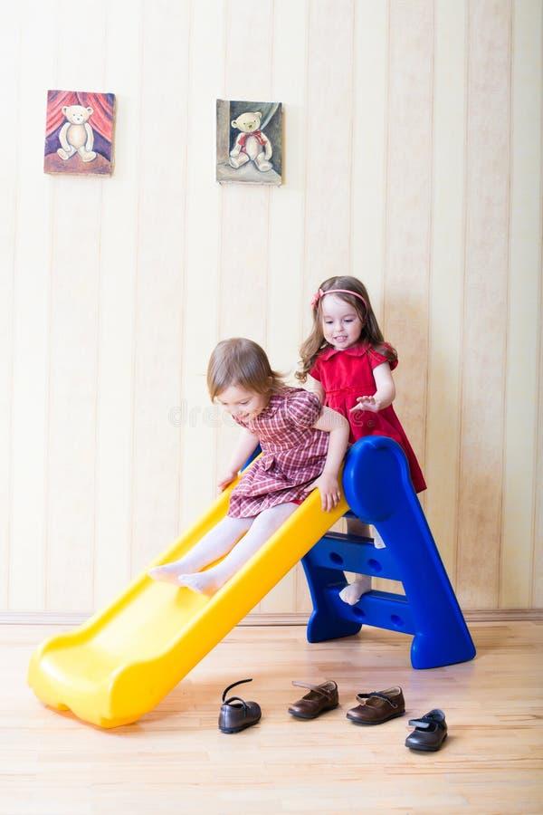 Deux filles ayant l'amusement placé sur la glissière de cour de jeu photos libres de droits