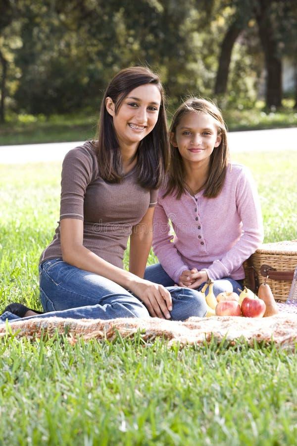 Deux filles ayant le pique-nique dans le stationnement photos stock