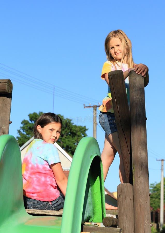 Deux filles ayant le repos sur la glissière image stock