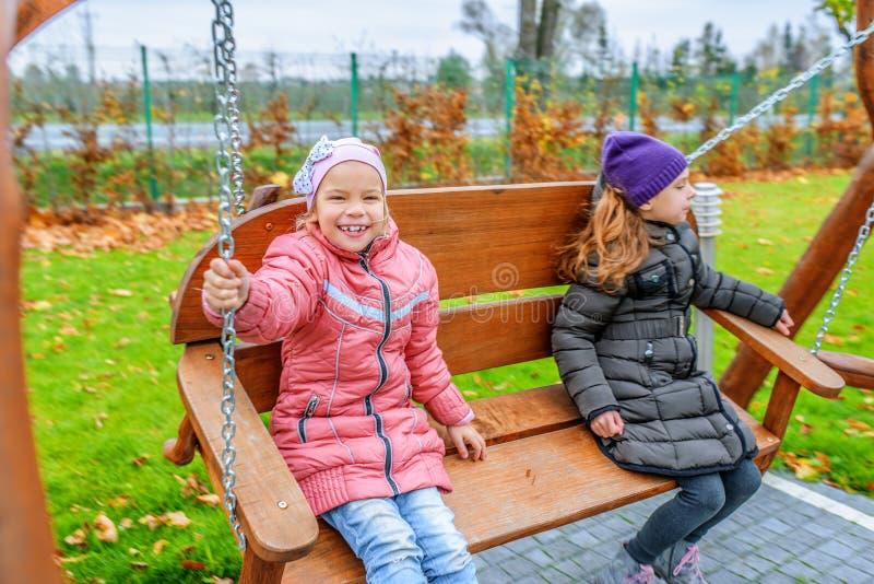 Deux filles balançant sur le terrain de jeu image libre de droits