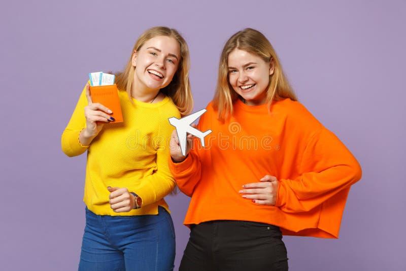 Deux filles blondes riantes de soeurs de jumeaux dans des vêtements colorés tiennent le passeport, billet de carte d'embarquement photo stock