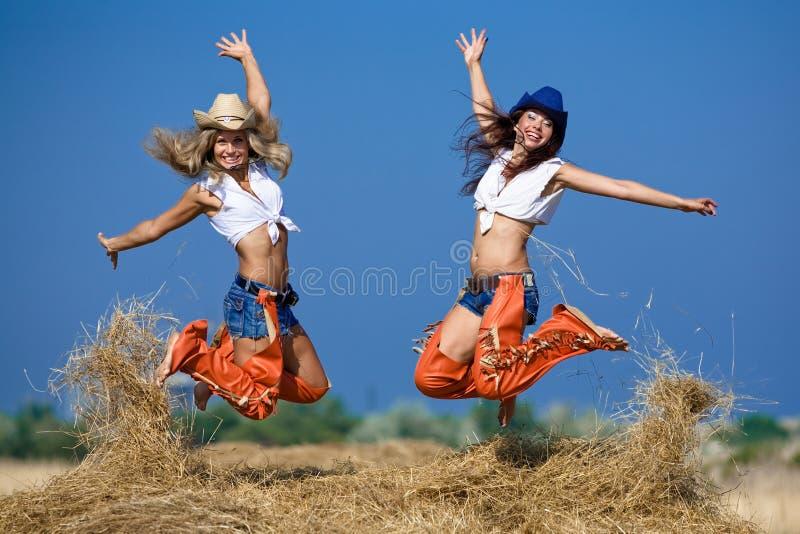 Deux filles branchant sur la meule de foin photos stock