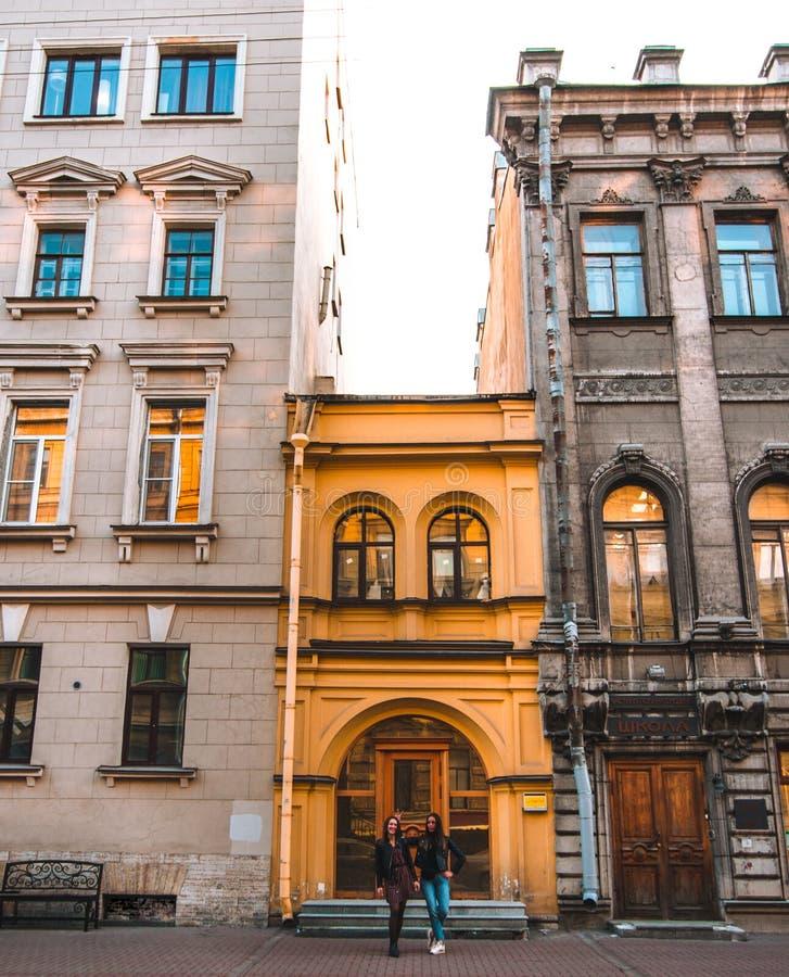 Deux filles caucasiennes attirantes se tiennent près de beaux vieux bâtiments européens un jour ensoleillé à St Petersburg jaune image stock