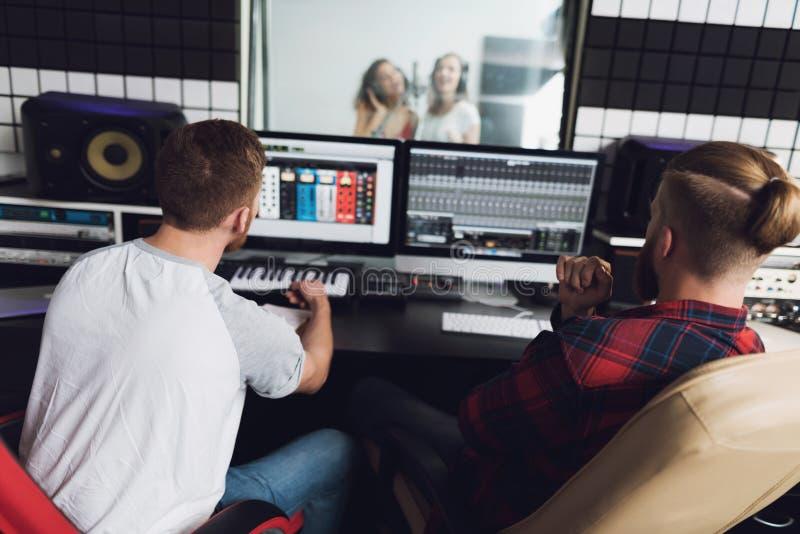 Deux filles chantent au studio d'enregistrement Derrière la console, deux ingénieurs du son sont reposants et observants l'enregi photo stock