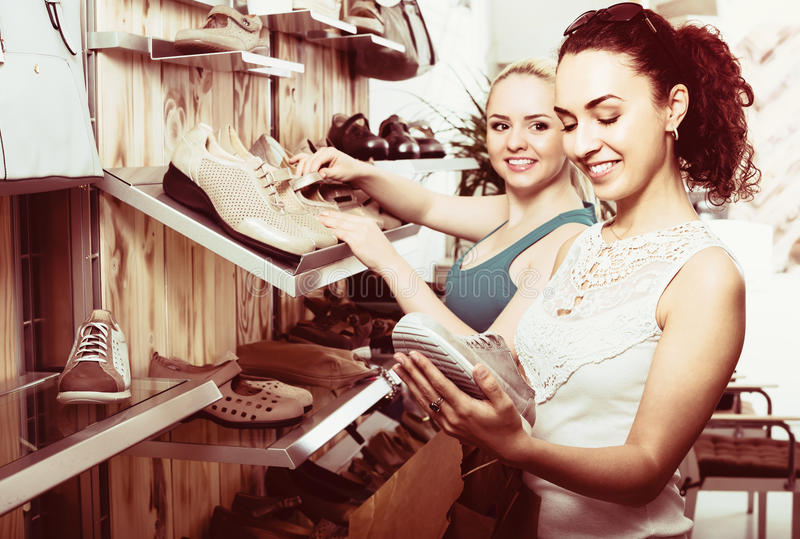 Deux filles choisissant des chaussures dans le magasin photographie stock