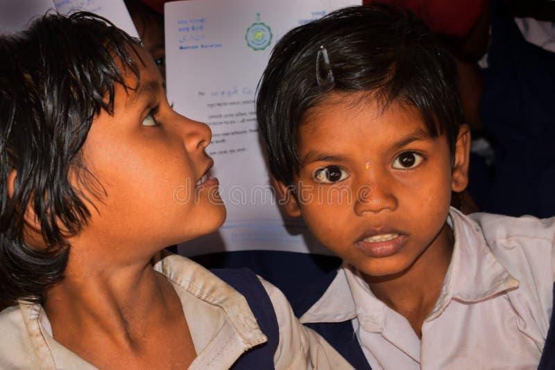Deux filles d'école d'une école primaire rurale du Bengale, regardaient vers l'objectif de caméra photographie stock