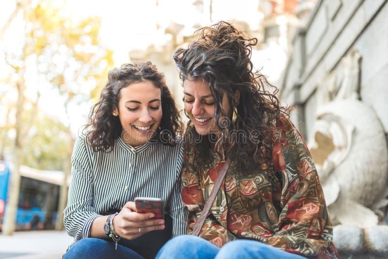 Deux filles d'ami utilisant l'ext?rieur de t?l?phone portable photographie stock libre de droits