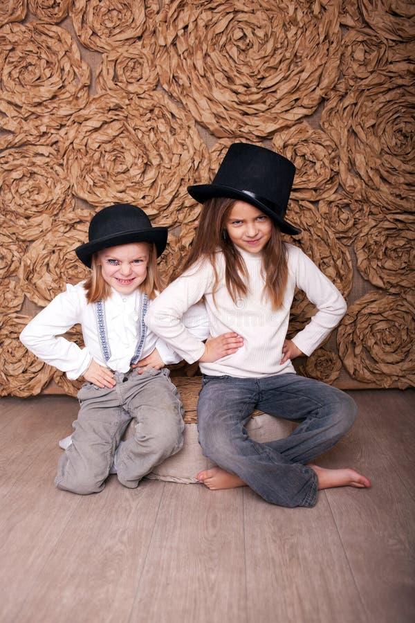 Deux filles dans des chapeaux noirs images stock