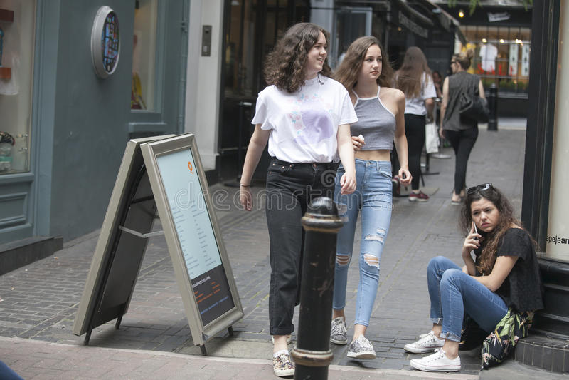 Deux filles dans des jeans passent par une fille s'asseyant sur le trottoir photo libre de droits