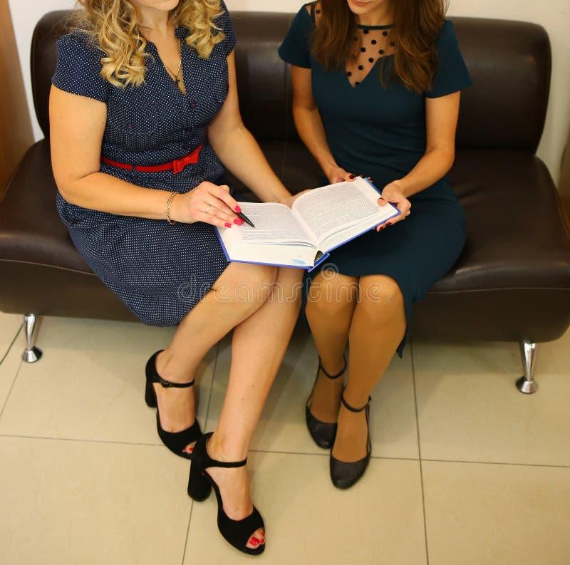 Deux filles dans les documents fonctionnants et de observations de bureau photographie stock libre de droits
