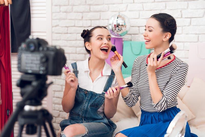 Deux filles de blogger de mode supportent beaucoup de brosses à l'appareil-photo images libres de droits