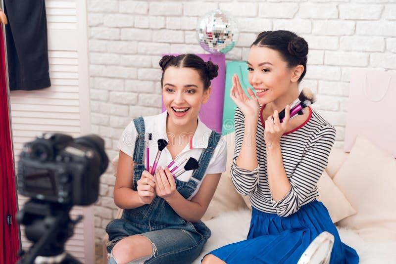 Deux filles de blogger de mode supportent beaucoup de brosses à l'appareil-photo image stock