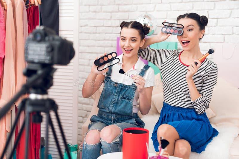 Deux filles de blogger de mode supportent des brosses et des fards à paupières à l'appareil-photo images libres de droits