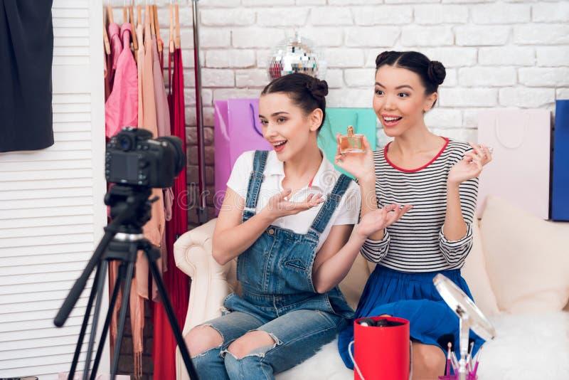 Deux filles de blogger de mode supportent le parfum à l'appareil-photo photo libre de droits