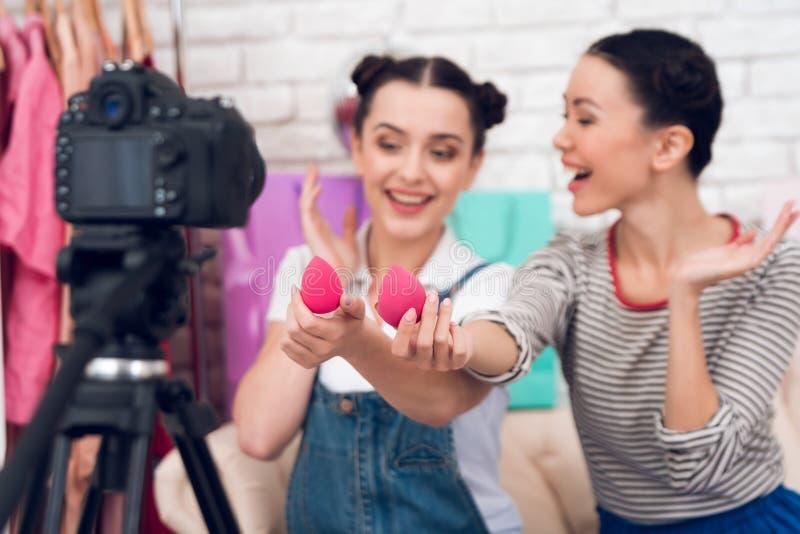 Deux filles de blogger de mode supportent les éponges rouges à l'appareil-photo photos stock